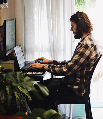 A person sitting at a desk using a computer. Office exercise self care tension ergonomics pain relief