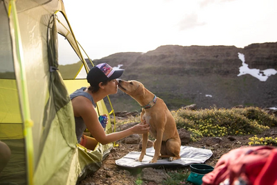 highlands sleeping pad dog sitting on pad licking man sitting in green tent in mountains