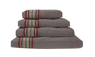 stack of yakima pet beds, the colors are brown, red, green, and yellow