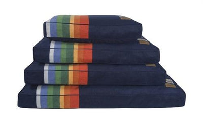 a stack of the crater lake dog beds. the colors are dark blue with orange, yellow, green, and light blue stripes