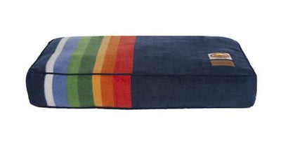 a single crater lake dog bed. the colors are dark blue with orange, yellow, green, and light blue stripes
