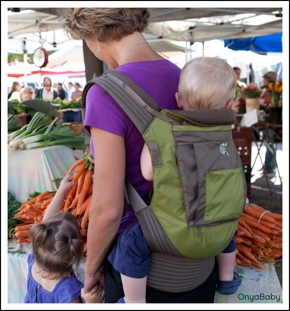 Mother babywearing in an Onya Baby Carrier at the farmers market
