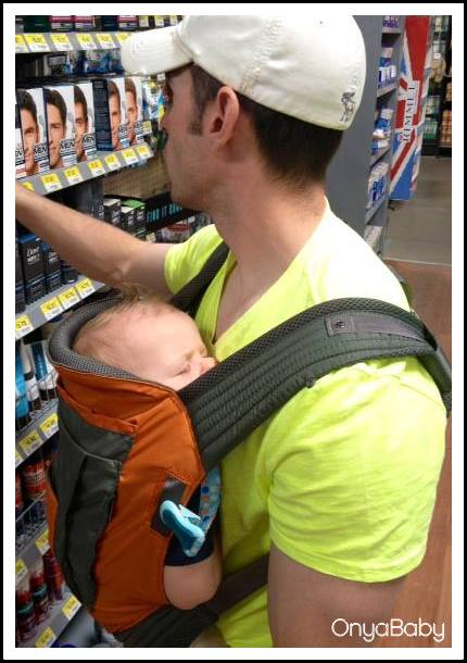 Father shopping with baby in Onya Baby carrier