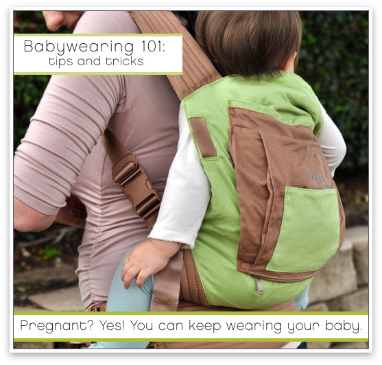 Pregnant mother demonstrating back carry with an Onya Baby Carrier