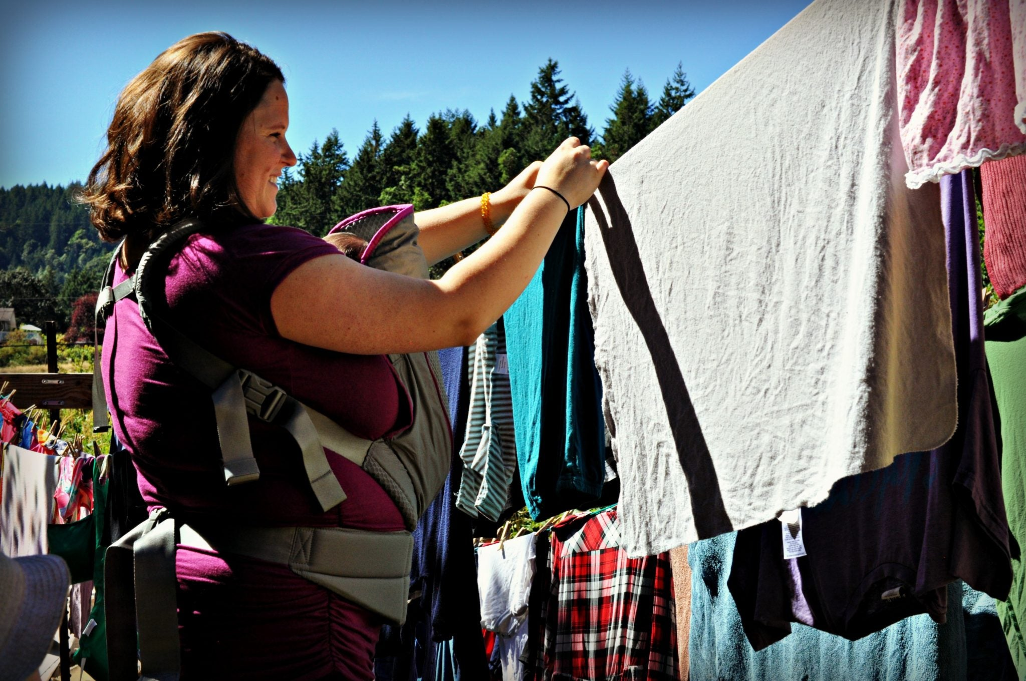 Mother hanging laundry to dry wearing baby in Onya carrier