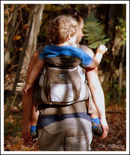 Parent hiking while babywearing with an Onya Baby Carrier