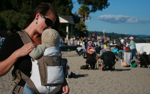 Mother kissing baby in Onya Baby Carrier at the beach