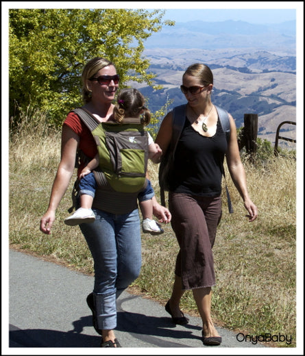 Parents out for a walk with child in an Onya Baby Carrier