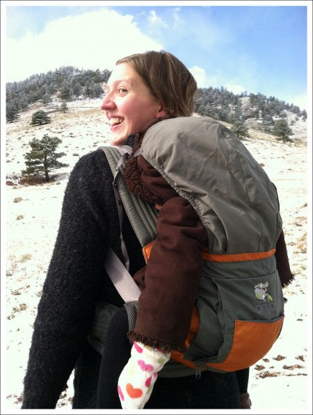 Woman with child in back carry position in Onya Baby Carrier