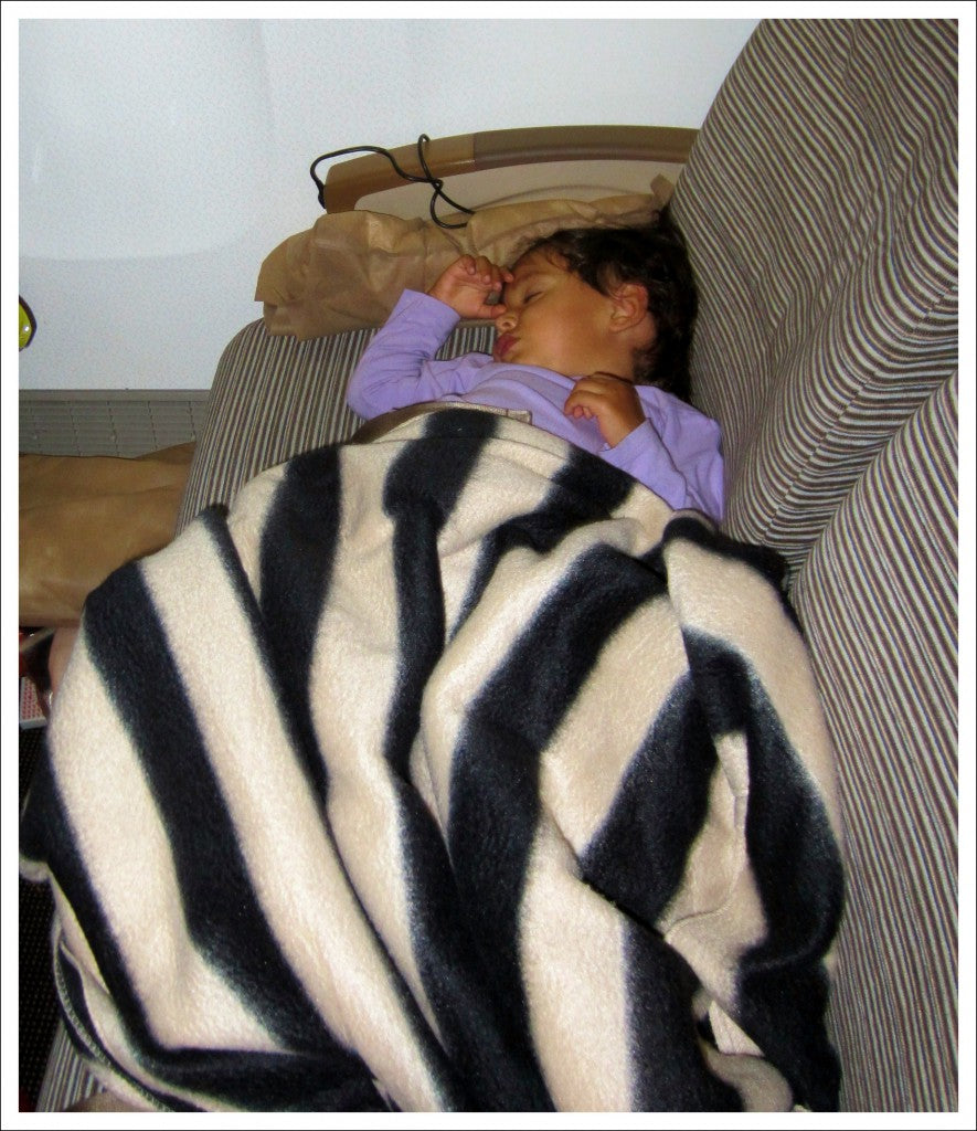 Tired baby sleeping on couch after helping mom pack for travels