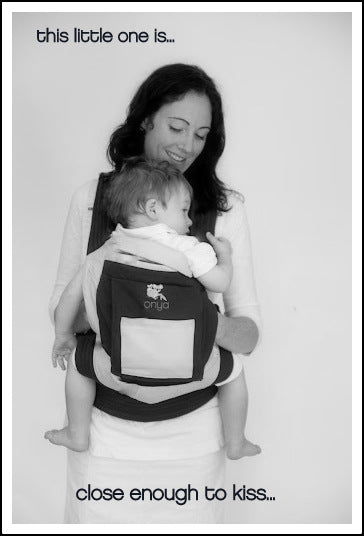 Mother demonstrating proper front carry with child in Onya Baby Carrier