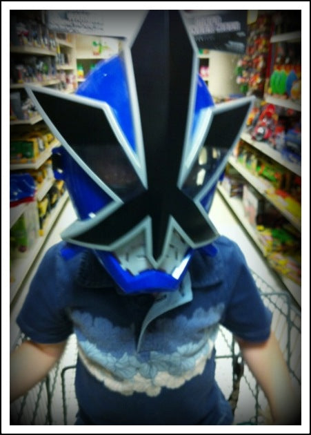 Parent and child having fun shopping with matching super hero masks