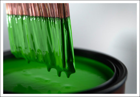 Paint brush dripping with green paint after being dipped