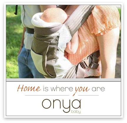 Mother using an Onya Baby Carrier to front carry infant