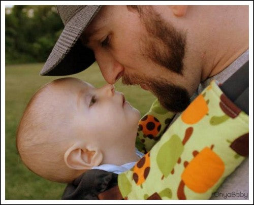 Father touching noses with his child in an Onya Baby Carrier