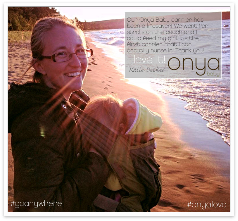 Mother nursing baby in Onya Baby Carrier at the beach