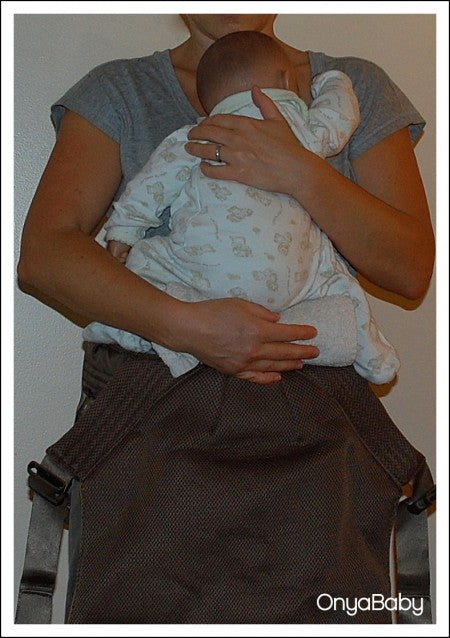 Woman placing baby into Onya Baby Carrier