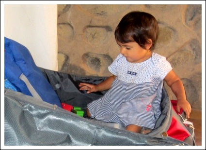 Child helping to pack and playing in suitcase