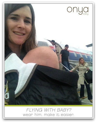 Mother with child in Onya Baby carrier boarding a plane