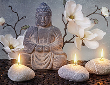 Buddha statue with candles and flowers