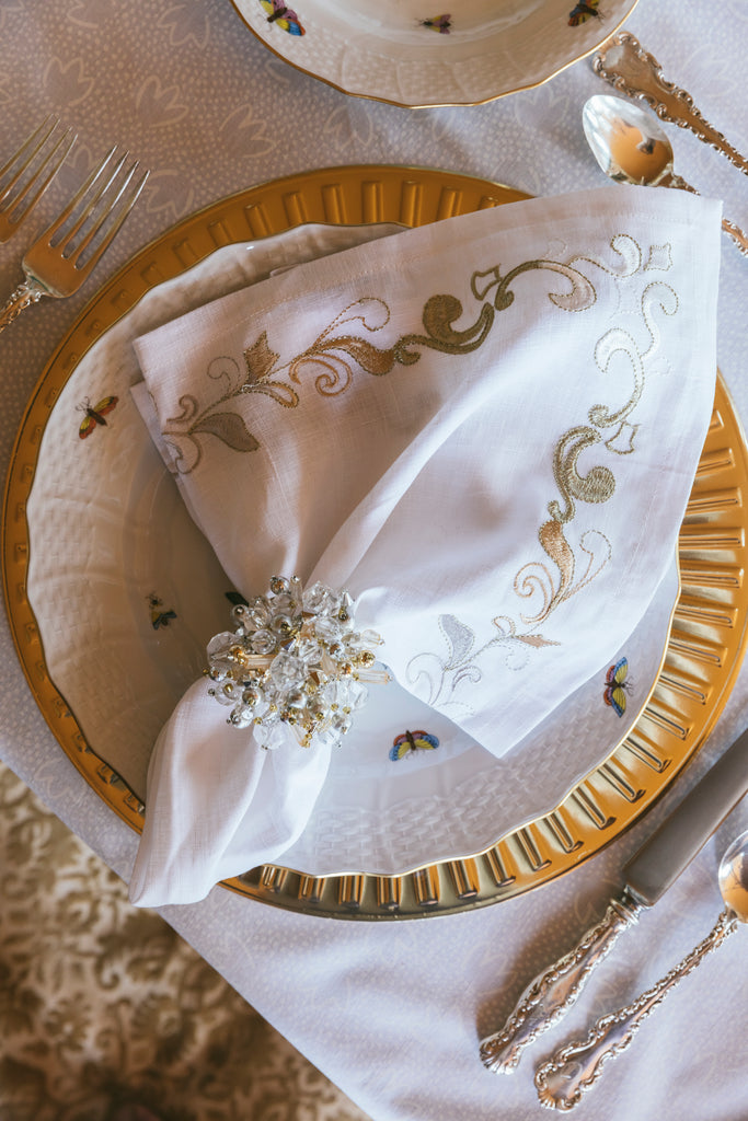 gold embroidered naplin and gold placemat place setting