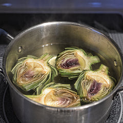 Place the halved artichokes in the boiling water; reduce heat, cover, and let them cook for 12-15 minutes