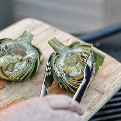 Brush the artichokes with some of the butter. Season them with salt and pepper. Squeeze some lemon juice on them.