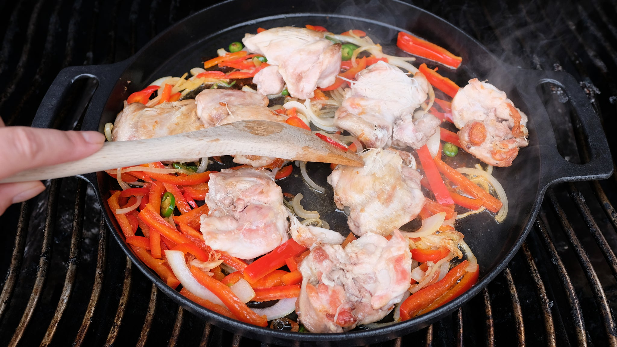 Sliced peppers, onion and hot peppers in pan with chicken & chicken juice