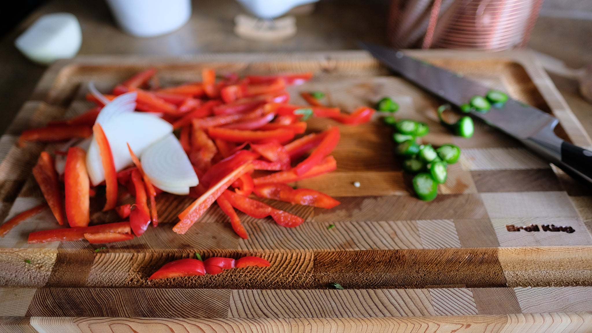 Onion, bell peppers and chili pepper, sliced on a cutting board