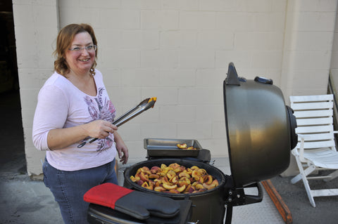Cindy grilling peaches on the Broil King Keg
