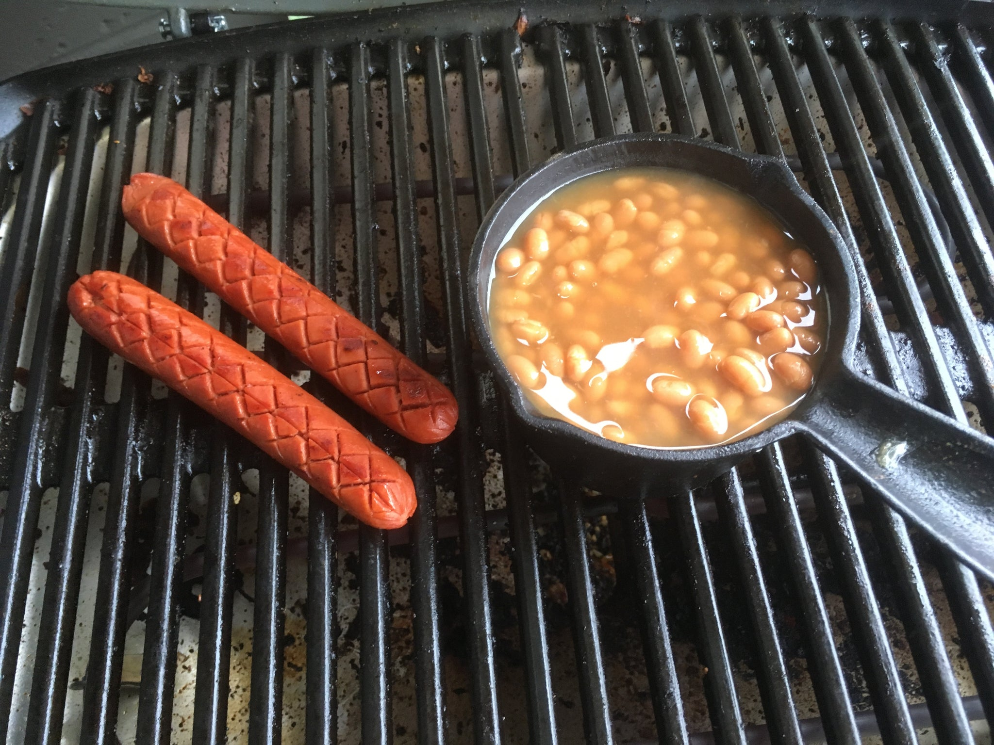 Hotdogs and baked beans on the barbecue
