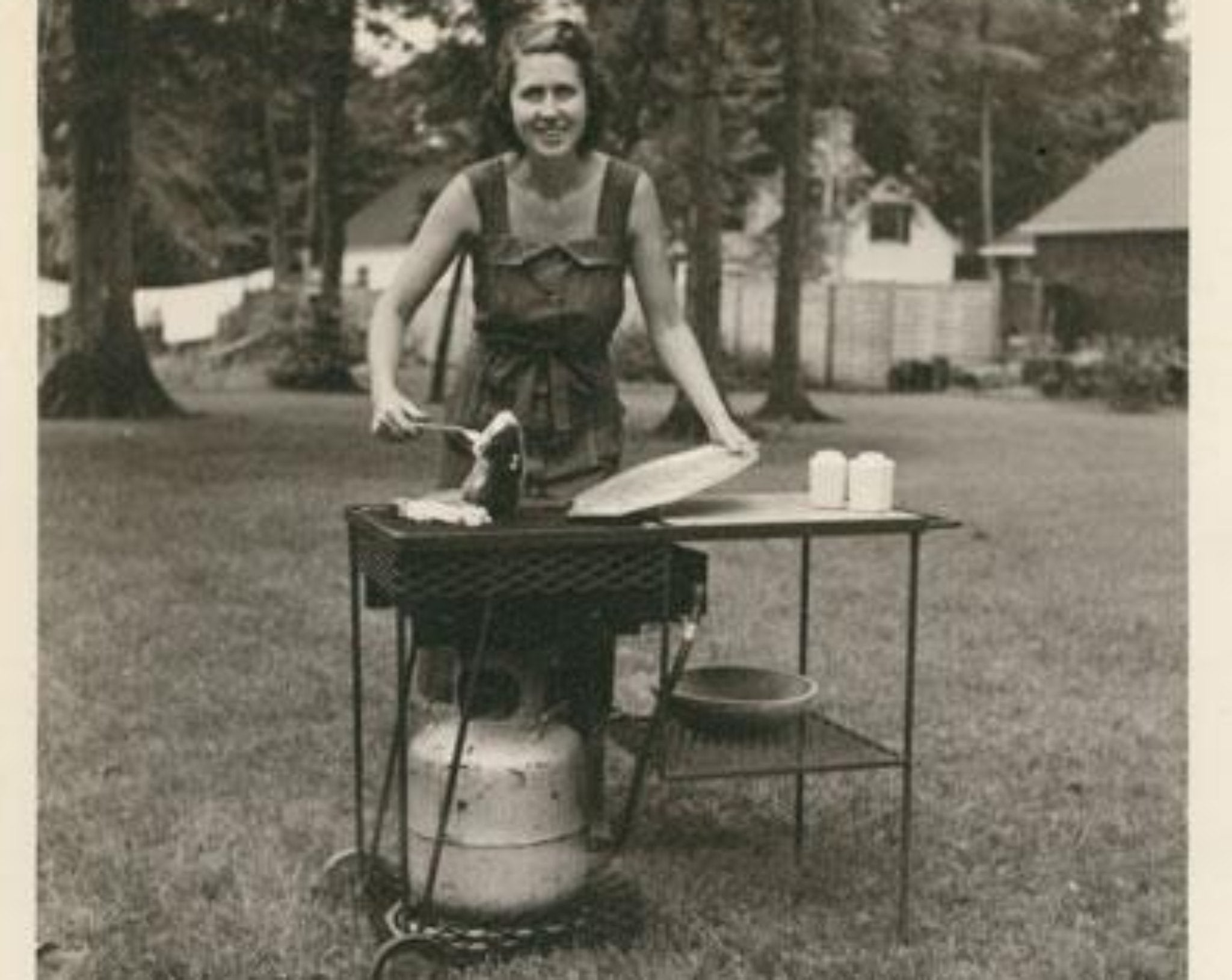Black and white picture of woman in backyard with barbecue
