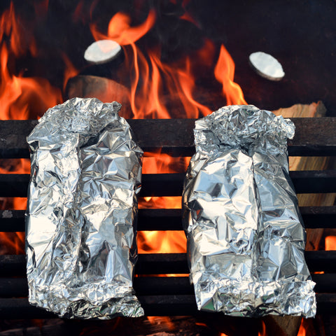 Place the packets on the grill over a campfire.