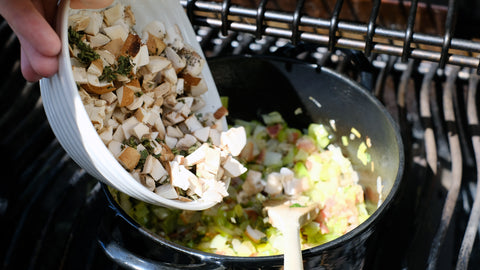 Adding chopped mushrooms to the crispy bacon, leek, onion and celery mix on the grill
