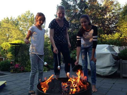 Kids roasting marshmallows over wood fire pit