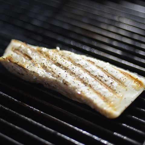 Put the fish on the grill.Flip the fish after a few minutes,