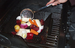 Brander porcelain coated grill topper with vegetables on top of a barbecues