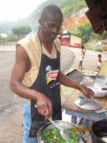 man cooking callallo on barbecue in jamaica