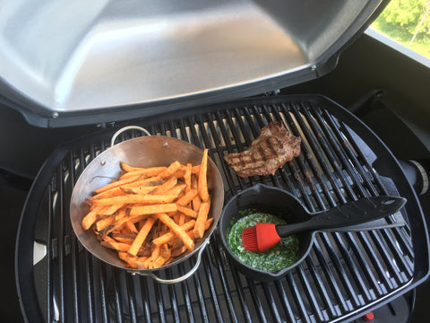 Brander Round Mini Grill Wok Basket on electric barbecue with steak and chimichurri sauce in cast iron grill pot