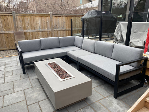 Thick concrete linear fire table with sleek straight sides and a long rectangular flame in the middle. This fire table has wide edges for glassware and fits perfectly on a deck or tight space. Available at Barbecues Galore: Burlington, Oakville, Etobicoke & Calgary