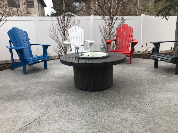 Outdoor GreatRoom Brooks Round Fire Table - Sitting outside on a patio with some lovely Adirondack chairs.  Great to add some ambiance and heat to our outdoor patio parties | Available at Barbecues Galore: Burlington, Oakville, Etobicoke & Calgary