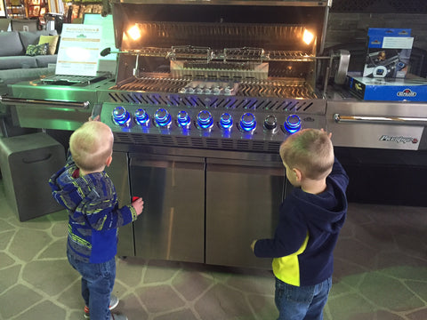 Two Children Enthralled with the glowy knobs on the Napoleon PRO665RSIB