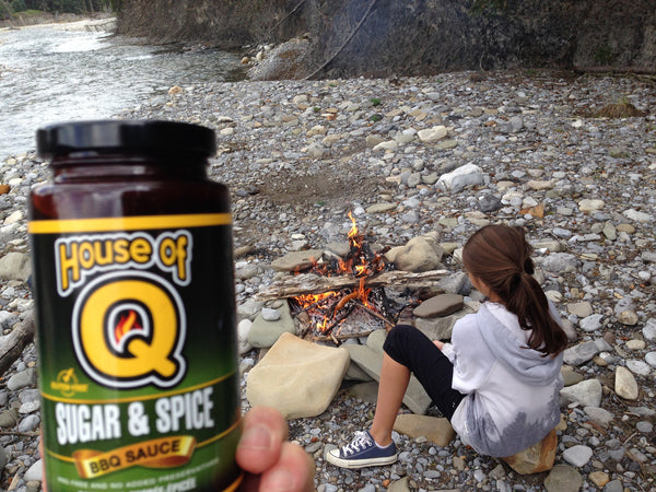 Girl enjoying House of Q Sugar & Spice BBQ Sauce on campfire smokies