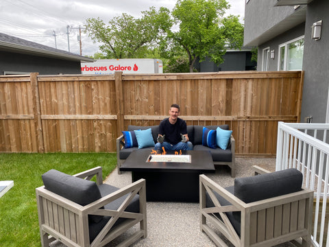 Outdoor Greatroom Archer Fire Table lit in a beautiful backyard with patio set | Barbecues Galore: Burlington, Oakville, Etobicoke & Calgary