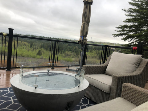 "Outdoor Great Room Cove 30"" Fire Bowl with burner cover and wind guard enjoying a rainy afternoon on the patio 