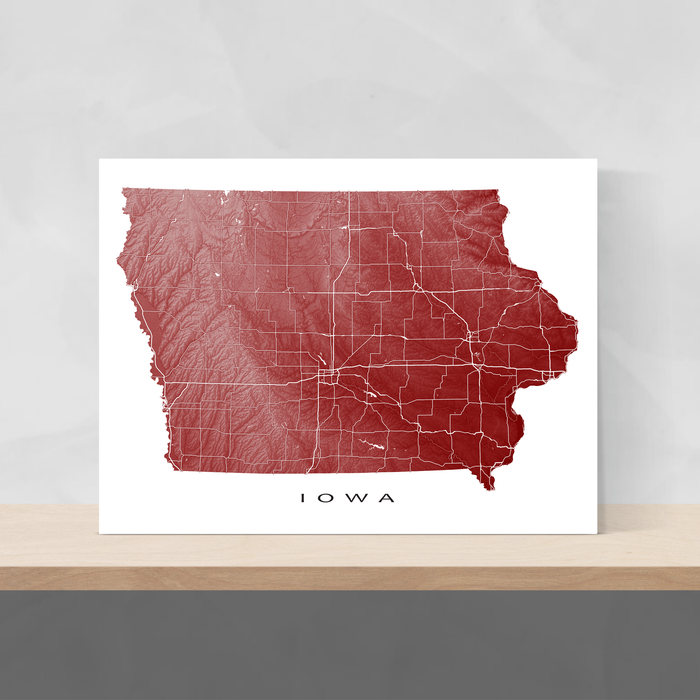 Iowa state map print with natural landscape and main roads in Merlot designed by Maps As Art.