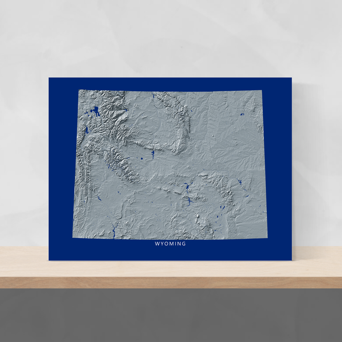 Wyoming state map print with natural landscape in greyscale and a navy blue background designed by Maps As Art.