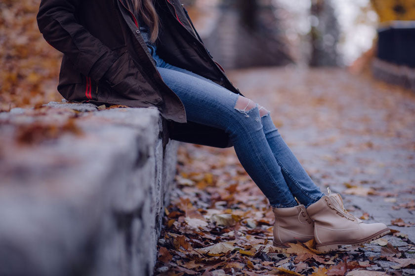 Woman in jeans, jacket, and boots sitting on a ledge surrounded by leaves