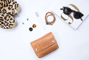 women's fashion accessories scattered on a white backdrop