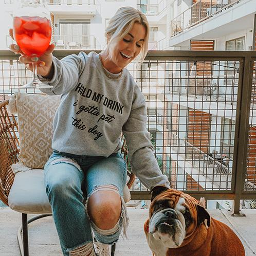 woman petting a dog and holding a drink while wearing a hold my drink sweatshirt